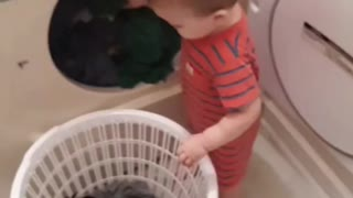 Helpful little boy assists mommy with the laundry