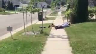 Man in blue falls off skateboard next to bush - Video