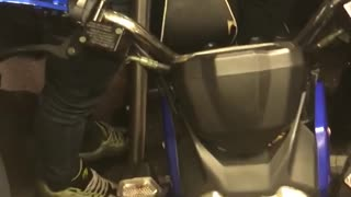 Guy brings blue motorcycle into subway
