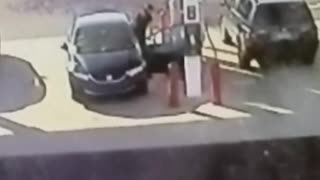 A man in black car breaks door at gas station - Video