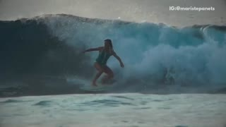 Music girl in green swimsuit surfer gets wiped out by wave