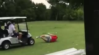 Red shirt grey shorts golfer hit by golf cart - Video