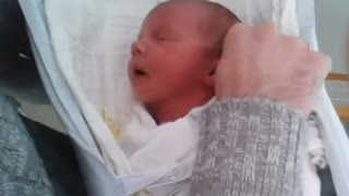 Newborn baby falls asleep in daddy's hands at the hospital