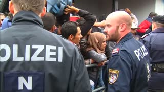 Migrants and refugees struggle to board train at station in Austria - Video