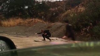 Guys trying to paddle and surf down muddy wet flooded street - Video