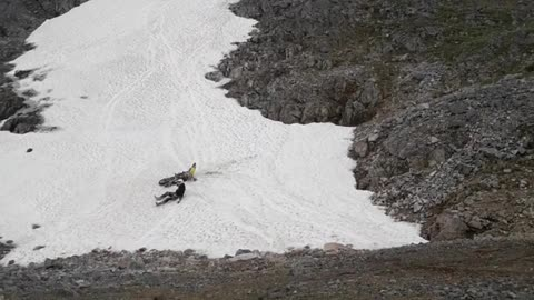Person guy drives motorcycle up white sand rocky hill falls off into sand