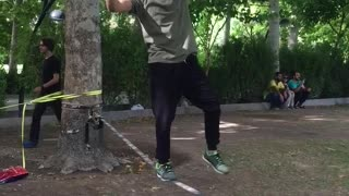 Guy does a backflip while walking a slackline and lands on his crotch