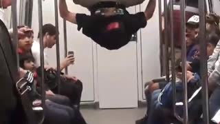 Guy hanging by feet in subway dancing upsides down hands