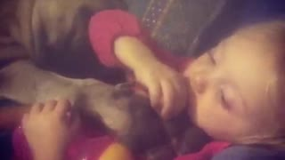 Little girl sweetly cuddles with her doggy