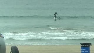 Man rides surfboard far out in ocean - Video