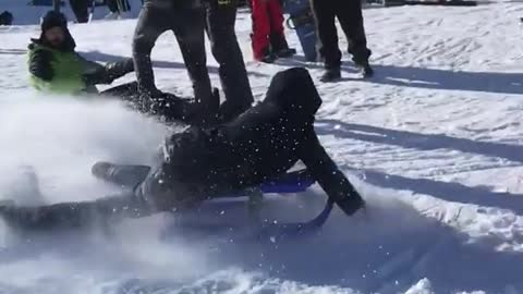 Boy on sled ramps into pile of blue orange objects