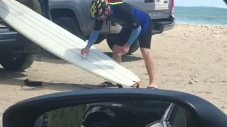 Yellow helmet guy waxes white surfboard out of back car