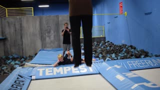 Trampoline flips into blonde friend