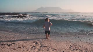 A small child is surprised by a wave