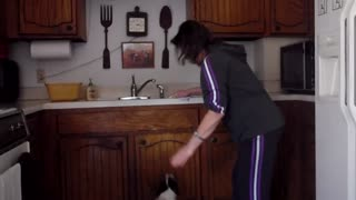 Woman Dribbles Jumping Dog That Loves Washing Dishes - Video