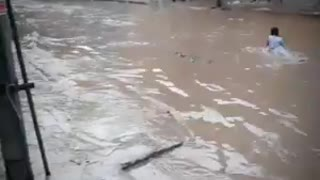 Boys playing on road in rainy water  - Video