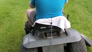 Boy rides lawnmower for the first time