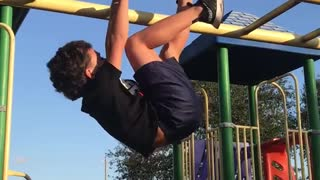 Kid in black run dmc shirt on yellow monkey bars falls down - Video