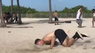 Shirtless man black shorts back flip fail in beach sand - Video