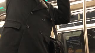 Man yells on subway train uses a bottle of cranberry juice as a microphone