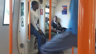 Man in blue swings from orange bars on train - Video