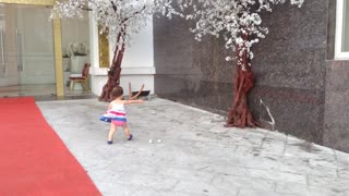 Little girl adorably chases paper in high wind gusts - Video