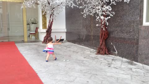 Little girl adorably chases paper in high wind gusts