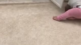 Baby in pink opens cabinet and falls