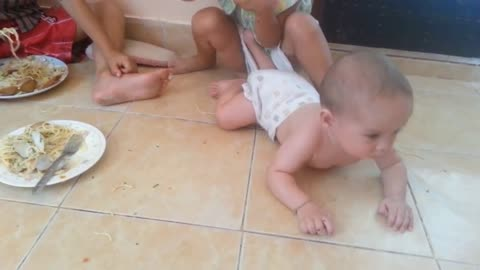 Baby hungerly attacks his sisters spaghetti