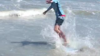 Kid blue shirt runs onto blue boogie board on beach falls into water - Video