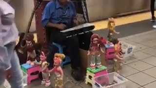Guy blue shirt playing xylophone with a bunch of dancing dolls around him