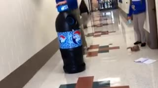 Teen jumps over huge blue soda bottle and falls in hallway  - Video