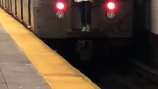 Guy white long riding behind moving subway train