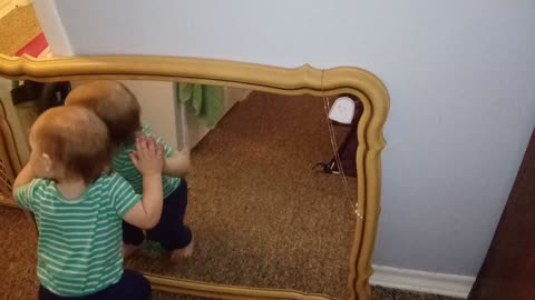 Baby adorably hugs and kisses his own reflection