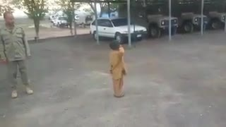 Trained small boy showing parade in front of army  - Video