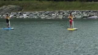 Two people on paddle boards in lake - Video