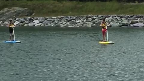 Two people on paddle boards in lake