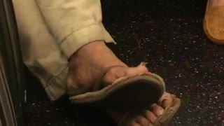 Zooming in on a mans toe nails on subway train  - Video