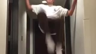 Kid in white shirt in hallway attempts backflip and fails  - Video