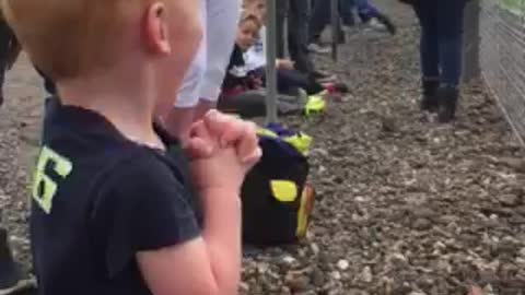 Boy Shakes With Excitement At Seeing Motorbikes Race For The First Time