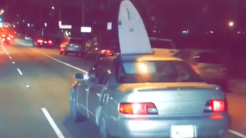 Brown car drives on road with surfboard sticking out of sunroof