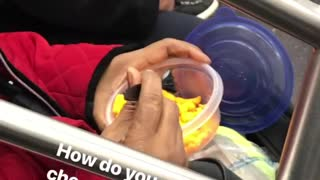 Woman eats cheetos with fork on subway train