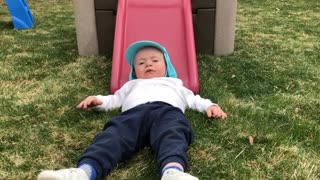 Little girl pushes little boy wearing blue hat down pink slide onto grass