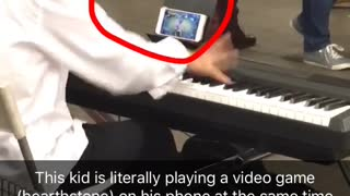 Kid white dress shirt playing piano in subway while playing hearthstone game on phone - Video