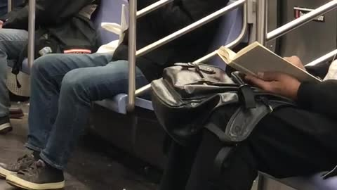 Man bites off apple skin and spits it out onto napkin on subway