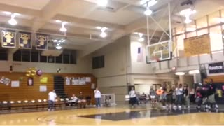 Girl makes basketball shot from behind her back at high school gym  - Video