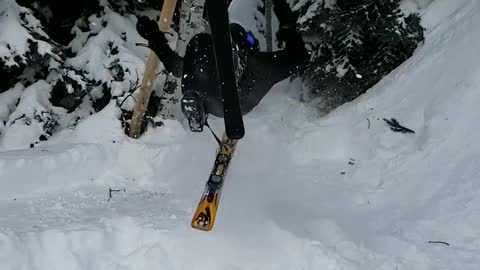 Skier backflips off small ramp, ski flies off right foot