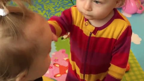Twin babies learn to be gentle with each other