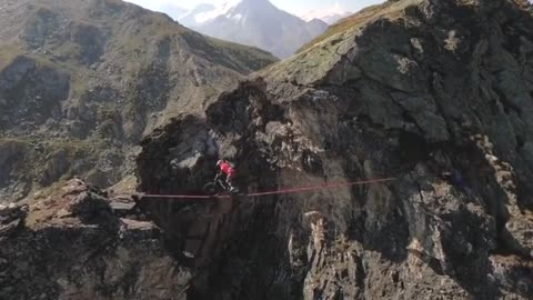 World champion rides bike over slackline in the Alps