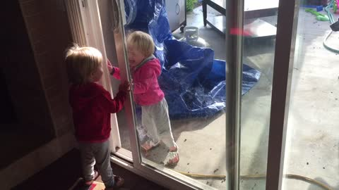 Identical twins play through glass door